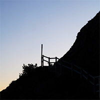A signpost and steep hillside silhouetted against the sky.